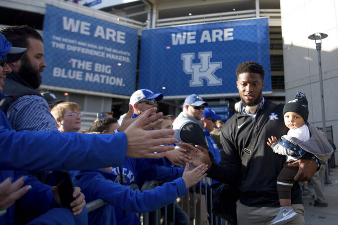 Kentucky linebacker Josh Allen (41) and his son Wesley greet fans during a pep rally before an NCAA college football game against Vanderbilt in Lexington, Ky., Saturday, Oct. 20, 2018. (AP Photo/Bryan Woolston)