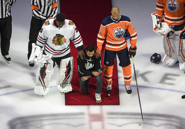 Minnesota Wild's Matt Dumba takes a knee during the national anthem flanked by Edmonton Oilers' Darnell Nurse, right, and Chicago Blackhawks' Malcolm Subban before an NHL hockey Stanley Cup playoff game in Edmonton, Alberta, Saturday, Aug. 1, 2020. (Jason Franson/The Canadian Press via AP)