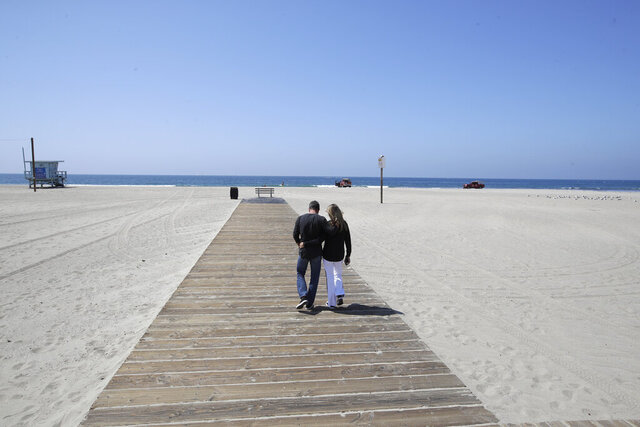A couple hugs as they walk down a boardwalk on a mostly deserted Santa Monica beach Sunday, March 29, 2020, in Los Angeles. With cases of coronavirus surging and the death toll increasing, lawmakers are pleading with cooped-up Californians to spend a second weekend at home to slow the spread of the infections. (AP Photo/Marcio Jose Sanchez)