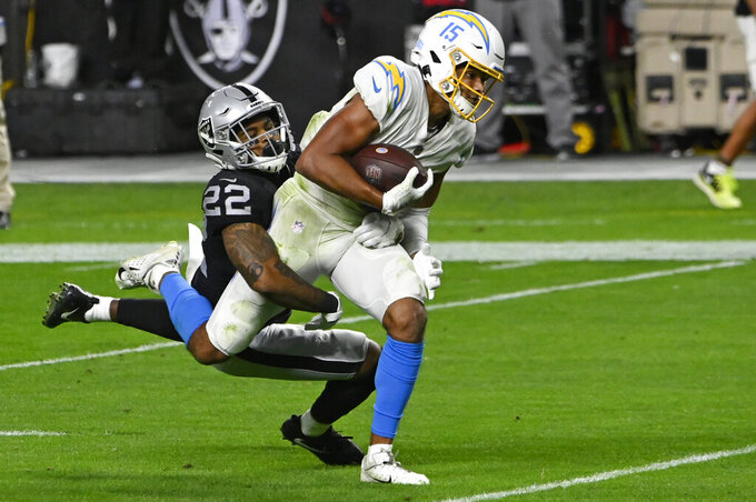 Las Vegas Raiders cornerback Keisean Nixon (22) tackles Los Angeles Chargers wide receiver Jalen Guyton (15) after Guyton made a catch in overtime of an NFL football game, Thursday, Dec. 17, 2020, in Las Vegas. (AP Photo/David Becker)