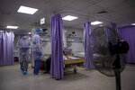 Palestinian doctors treat patients at the emergency room of the al-Quds Hospital in Gaza City, Monday, Sept. 7, 2020. Dozens of front-line health care workers have been infected, dealing a new blow to overburdened hospitals. (AP Photo/Khalil Hamra)