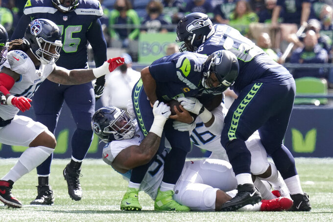 Seattle Seahawks quarterback Russell Wilson is tackled by Tennessee Titans' Denico Autry, center-right, and Jeffery Simmons, center-left, during the first half of an NFL football game, Sunday, Sept. 19, 2021, in Seattle. (AP Photo/Elaine Thompson)