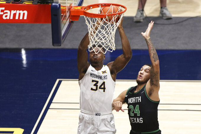 West Virginia forward Oscar Tshiebwe (34) shoots while defended by North Texas forward Zachary Simmons (24) during the first half of an NCAA college basketball game Friday, Dec. 11, 2020, in Morgantown, W.Va. (AP Photo/Kathleen Batten)