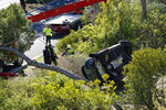 A vehicle rests on its side after a rollover accident involving golfer Tiger Woods Tuesday, Feb. 23, 2021, in the Rancho Palos Verdes suburb of Los Angeles. Woods suffered leg injuries in the one-car accident and was undergoing surgery, authorities and his manager said. (AP Photo/Marcio Jose Sanchez)