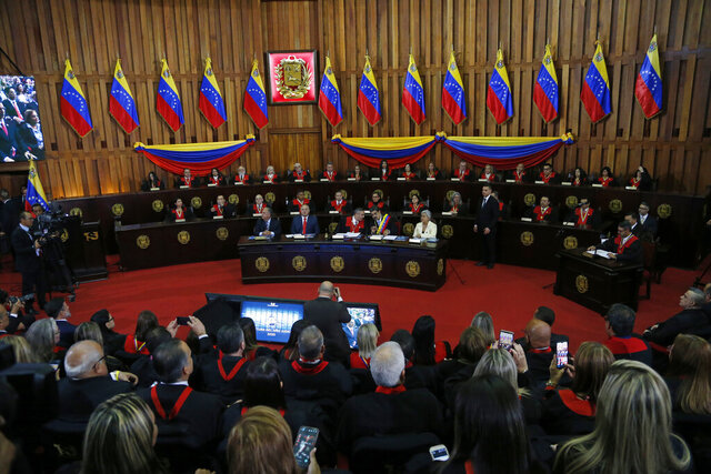 FILE - In this  Jan. 31, 2020 file photo, Venezuelan President Nicolas Maduro, sitting at desk second from right, speaks with Supreme Court President Maikel Moreno at the Supreme Court before giving his annual presidential address in Caracas, Venezuela. The court ordered on Monday, June 15, 2020, the takeover of Democratic Action, one of the nation's oldest and most influential political parties, which is now opposed to the government. (AP Photo/Ariana Cubillos, File)