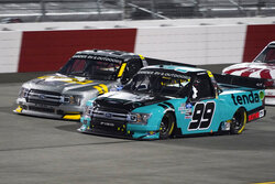 Ben Rhodes (99) and Grant Enfinger (98) compete for the lead at the start of the third stage during the NASCAR Truck Series auto race Thursday, Sept. 10, 2020, in Richmond, Va. (AP Photo/Steve Helber)