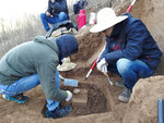 In this Sunday, Dec. 10, 2017 photo provided by Zhaoyu Zhu, scientists examine a pointed piece of quartzite rock that was unearthed from the oldest layer of dirt at a site in the Loess Plateau in China. In a report released on Wednesday, July 11, 2018, scientists believe stone tools like this could have belonged to our evolutionary forerunners that lived 2.1 million years ago. (Zhaoyu Zhu via AP)