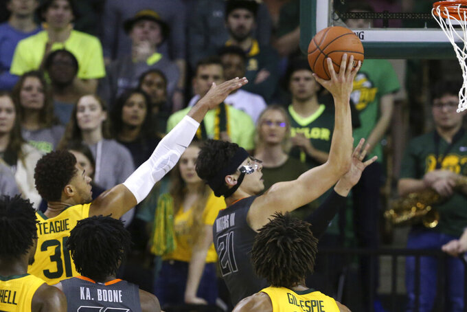 Oklahoma State guard Lindy Waters III, right, scores past Baylor guard MaCio Teague, left, during the second half of an NCAA college basketball game Saturday, Feb. 8, 2020, in Waco, Texas. (AP Photo/Rod Aydelotte)