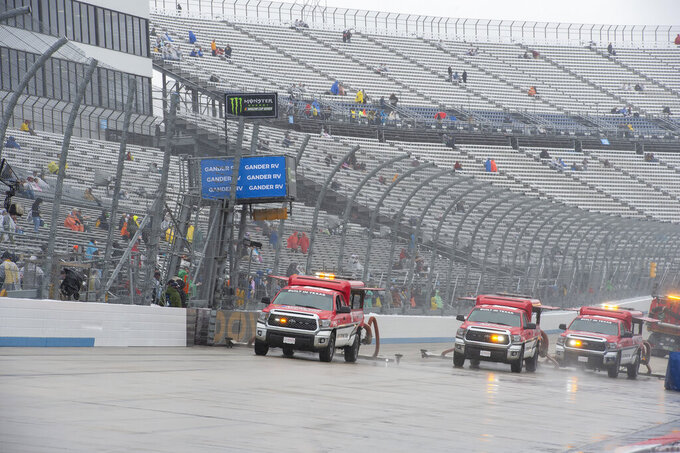 Track drying teams work to dry the track before the start of a NASCAR Cup series auto race Sunday, May 5, 2019, at Dover International Speedway in Dover, Del. (AP Photo/Jason Minto)