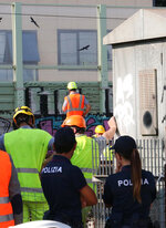 Police stand by as workers check electrical cables where a suspected arson fire occurred, on the tracks between Rovezzano and Campo di Marte train station, in Florence, Italy, Monday, July 22, 2019. The suspected arson fire has forced cancellations of at least 42 high-speed trains in Italy on the heavily-traveled Milan-Naples corridor. (Claudio Giovannini/ANSA via AP)