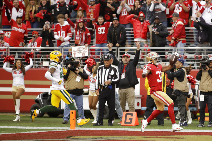 Fans cheer as San Francisco 49ers running back Raheem Mostert, bottom right, scores against the Green Bay Packers during the first half of the NFL NFC Championship football game Sunday, Jan. 19, 2020, in Santa Clara, Calif. (AP Photo/Ben Margot)
