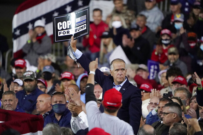 Sen. Tom Tillis, R-N.C. holds a sign as President Donald Trump speaks at a campaign rally, Saturday, Sept. 19, 2020 at the Fayetteville Regional Airport in Fayetteville, N.C. (AP Photo/Chris Carlson)