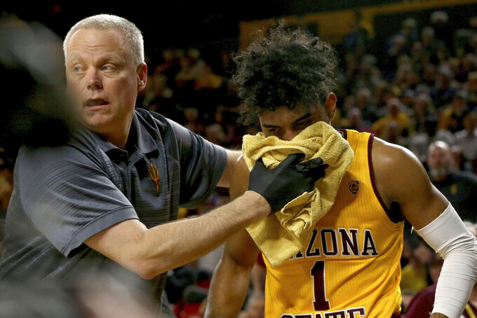 Arizona State's trainer attends to Remy Martin after getting elbowed twice against Oregon during the first half of an NCAA college basketball game Thursday, Feb. 20, 2020, in Tempe, Ariz. (AP Photo/Darryl Webb)