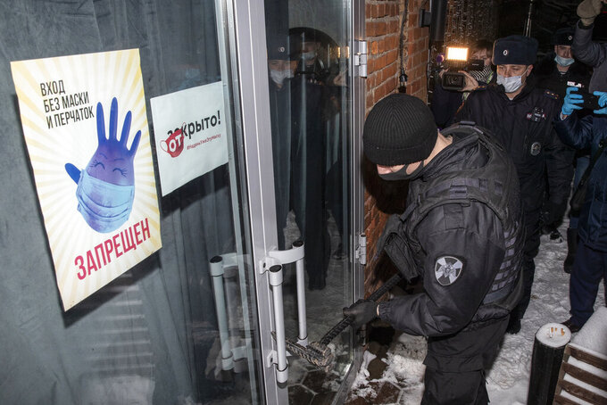 FILE - In this Dec. 26, 2020, file photo, Russian police break the door of a bar for violating a mayoral decree that said businesses must close at 11 p.m. in Moscow, Russia, due to the coronavirus. Some owners of businesses disobeyed the virus restrictions in Moscow and St. Petersburg. (AP Photo/Pavel Golovkin, File)