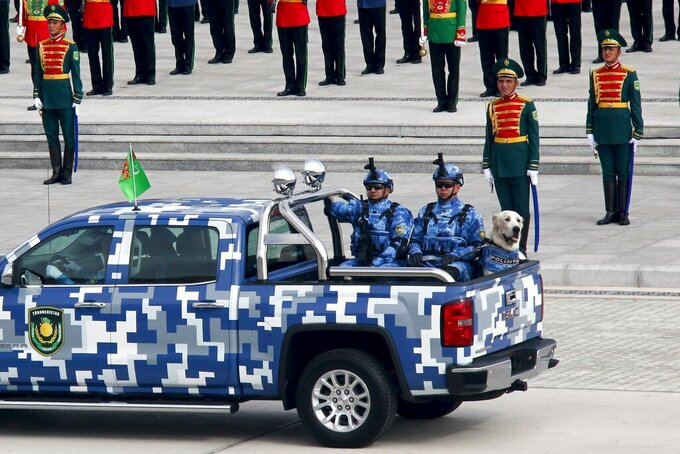 Turkmenistan's police officers with a shepherd dog Alabay ride a pickup during a military parade celebrating the country's 30th independence anniversary in Ashgabat, Turkmenistan, Monday, Sept. 27, 2021. The pomp-filled parade took place in Ashgabat, the capital of the gas-rich former Soviet nation in Central Asia. Aside from troops and military equipment, the parade featured employees of state ministries and institutions demonstrating their achievements and Alabai dogs, which accompanied soldiers on military vehicles. (AP Photo/Alexander Vershinin)