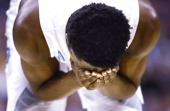 Duke forward RJ Barrett cover his face after getting hit during the second half of an NCAA men's college basketball tournament East Region semifinal against Virginia Tech in Washington, Friday, March 29, 2019. (AP Photo/Patrick Semansky)