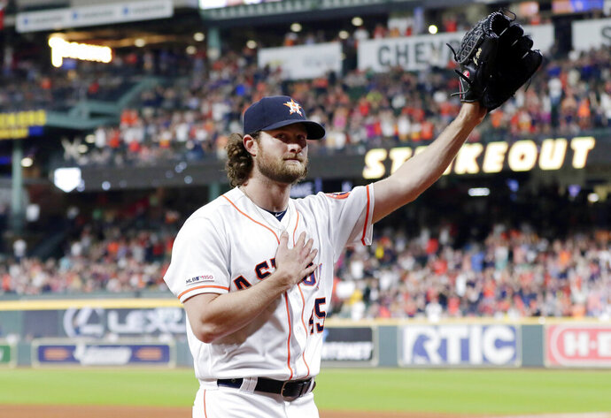 Houston Astros starting pitcher Gerrit Cole waves to the crowd as he leaves the mound after striking out Texas Rangers designated hitter Shin-Soo Choo for his 300th season strikeout during the sixth inning of a baseball game Wednesday, Sept. 18, 2019, in Houston. (AP Photo/Michael Wyke)