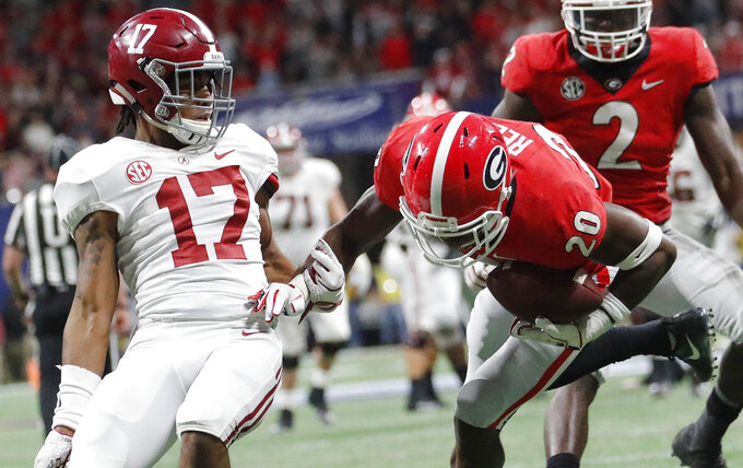 Georgia defensive back J.R. Reed (20) picks off a pass intended for Alabama wide receiver Jaylen Waddle (17) during the second half of the Southeastern Conference championship NCAA college football game, Saturday, Dec. 1, 2018, in Atlanta. (AP Photo/John Bazemore)