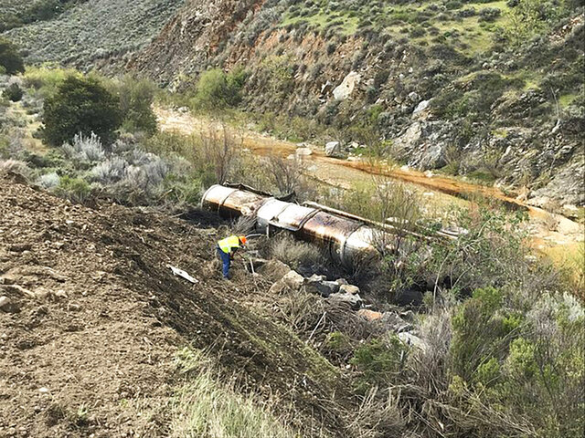 This photo tweeted by the Santa Barbara County Fire Department shows a worker for a clean up company working to mitigate the crude oil release from an oil tanker after it was derailed and overturned near Santa Maria, Calif., Saturday, March 21, 2020. The tanker truck overturned down an embankment Saturday, spilling up to 6,000 gallons of crude oil into a river that flows into a dam and reservoir near the city of Santa Maria, authorities said. (Santa Barbara County Fire via AP)