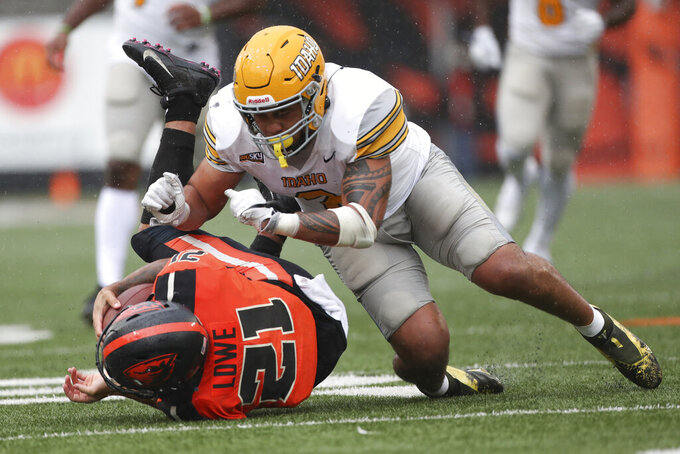 Oregon State running back Trey Lowe (21) is tackled by Idaho linebacker Fa'Avae Fa'Avae (2) during the second half of an NCAA college football game Saturday, Sept. 18, 2021, in Corvallis, Ore. Oregon State won 42-0. (AP Photo/Amanda Loman)