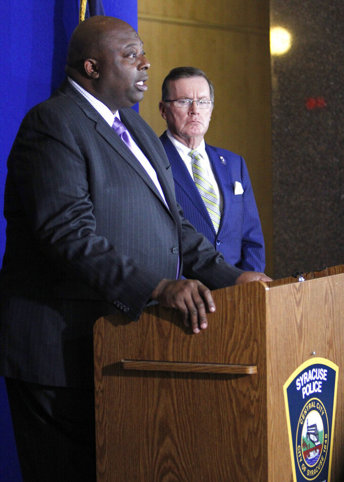 Syracuse Police Chief Kenton T. Buckner, left, and Onondaga County District Attorney William J. Fitzpatrick, right, attend a news conference at the Syracuse Police Department in Syracuse, N.Y., Thursday, Feb. 21, 2019, about Syracuse men's NCAA college basketball head coach Jim Boeheim's involvement in a fatal car accident where he struck and killed a man standing along an interstate in Syracuse. Boeheim struck and killed a man along an interstate late Wednesday night as he tried to avoid hitting the man's disabled vehicle, police say. (AP Photo/Nick Lisi)