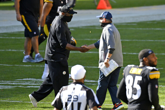 Pittsburgh Steelers head coach Mike Tomlin and Denver Broncos head coach Vic Fangio shake hands following a Steelers win in an NFL football game in Pittsburgh, Sunday, Sept. 20, 2020. (AP Photo/Don Wright)