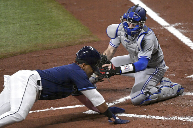 Tampa Bay Rays' Yandy Diaz is tagged out at home plate by Toronto Blue Jays catcher Danny Jansen during the first inning of a baseball game Friday, April 23, 2021, in St. Petersburg, Fla. (AP Photo/Phelan M. Ebenhack)