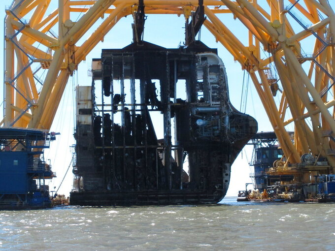 Interior decks of the capsized cargo ship Golden Ray are exposed on Monday, April 26, 2021, after the engine room section was cut away and separated from the rest of the shipwreck by a towering crane, offshore of St. Simons Island, Ga. The South Korean vessel capsized with roughly 4,200 vehicles in its cargo decks in September 2019. The engine room section is the fourth giant chunk of the ship to be cut away and removed since demolition began in November 2020. (AP Photo/Russ Bynum)