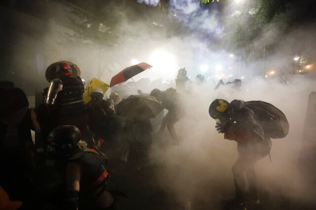 FILE - In this July 26, 2020, file photo, federal officers launch tear gas at demonstrators during a Black Lives Matter protest at the Mark O. Hatfield U.S. Courthouse in Portland, Ore. The Associated Press found that there is no government oversight of the manufacture and use of tear gas. Instead, the industry is left to regulate itself. (AP Photo/Marcio Jose Sanchez, File)