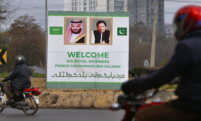 Pakistani motorcyclists pass by a billboard welcoming Saudi Arabia's Crown Prince Mohammed bin Salman displayed on the occasion of the visit by Saudi Arabia's crown prince to Pakistan, in Islamabad, Pakistan, Sunday, Feb. 17, 2019. Saudi Crown Prince Mohammed bin Salman will arrive in Islamabad on Sunday evening on an official visit that is expected to include the signing of agreements for billions of dollars of investment in Pakistan. (AP Photo/Anjum Naveed)