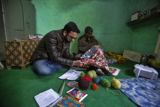Kashmiri entrepreneur Basharat Ashraf, left, and artisan Imtayaz Ahmad work inside their workshop in Srinagar, Indian controlled Kashmir, Wednesday, Nov. 18, 2020. An Indian designer and architect couple have launched a campaign called 'Empowerment through Craft' to help traditional artisans restart sales and trade on an online platform called Direct Create. During a time when the pandemic and a subsequent nationwide lockdown that halted the economy, the online marketing and collaboration platform has come as a huge relief for craftsmen who live in remote parts of the country and have traditionally relied on exhibitions and physical markets to showcase and sell their arts and crafts. (AP Photo/Mukhtar Khan)