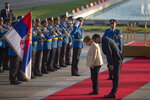 German Chancellor Angela Merkel, center, bows to the Serbian flag while being accompanied by Serbia's president Aleksandar Vucic, front right, in Belgrade, Serbia, Monday, Sept. 13, 2021. Merkel is on a farewell tour of the Western Balkans, as she announced in 2018 that she wouldn't seek a fifth term as Germany's Chancellor. (AP Photo/Marko Drobnjakovic)