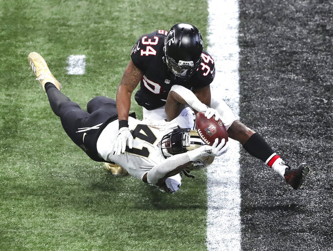 New Orleans Saints running back Alvin Kamara dives into the endzone past Atlanta Falcons cornerback Darqueze Dennard for a touchdown during the second half of an NFL football game on Sunday, Dec. 6, 2020, in Atlanta. (Curtis Compton/Atlanta Journal-Constitution via AP)