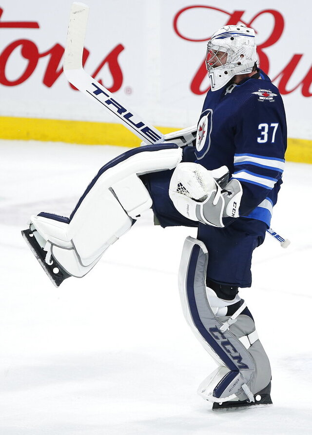 Winnipeg Jets goaltender Connor Hellebuyck celebrates a 3-0 shutout against the Washington Capitals in an NHL hockey game Thursday, Feb. 27. 2020, in Winnipeg, Manitoba. (John Woods/The Canadian Press via AP)