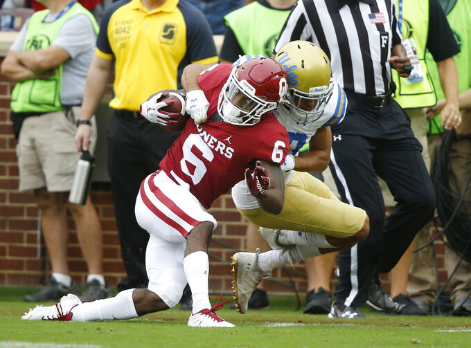 Oklahoma cornerback Tre Brown (6) is brought down by UCLA defensive back Nate Meadors (22) after an 86 yard kick off return in the first quarter of an NCAA college football game in Norman, Okla., Saturday, Sept. 8, 2018. (AP Photo/Sue Ogrocki)
