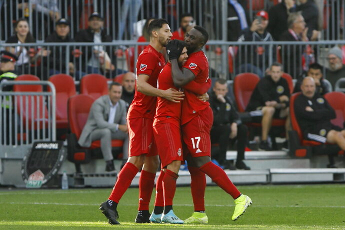 Toronto FC midfielder Alejandro Pozuelo, middle, celebrates his goal against the Columbus Crew with defender Omar Gonzalez, left, and forward Jozy Altidore (17) during the second half of an MLS soccer match in Toronto, Sunday, Oct. 6, 2019. (Cole Burston/The Canadian Press via AP)