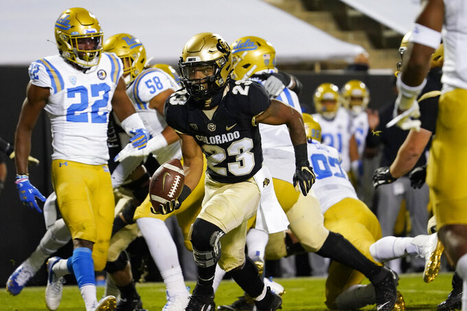 Colorado running back Jarek Broussard, front center, rolls into the end zone for a touchdown against UCLA in the first half of an NCAA college football game Saturday, Nov. 7, 2020, in Boulder, Colo. (AP Photo/David Zalubowski)