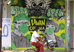 A woman rides her bicycle past a coronavirus awareness mural depicting medical workers in Bangkalan, Madura Island, Indonesia, Monday, April 6, 2020. The new coronavirus causes mild or moderate symptoms for most people, but for some, especially older adults and people with existing health problems, it can cause more severe illness or death. Writings on the mural read