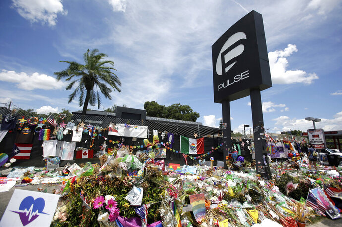 FILE - In this July 11, 2016, file photo, a makeshift memorial continues to grow outside the Pulse nightclub in Orlando, the day before the one month anniversary of a mass shooting, in Orlando, Fla. A group of survivors and family members of those killed have formed an organization to oppose the building of a private museum to honor the victims of a mass shooting at the Florida nightclub three years ago. Members of the Community Coalition Against a Pulse Museum say the nightclub should be torn down and the nightclub's owner shouldn't build a private museum. (AP Photo/John Raoux, File)