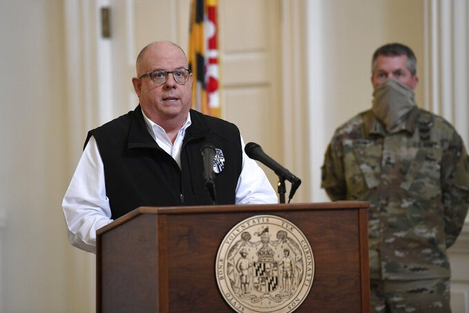 Maryland Gov. Larry Hogan speaks during a news conference in Annapolis, Md., Friday, April 10, 2020. Hogan provided several updates on the state's response to the coronavirus pandemic, including key budget actions and efforts to bolster the process to apply for unemployment. Adjutant General Major Gen. Timothy Gowen listens at right. (AP Photo/Susan Walsh)