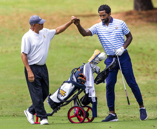 North Carolina A&T head golf coach Richard Watkins, left, bumps fists with and North Carolina A&T's J.R. Smith on the ninth hole during the second round of the Phoenix Invitational golf tournament in Burlington, N.C., Tuesday, Oct. 12, 2021. Smith spent 16 years playing in the NBA, winning two world championships. (Woody Marshall/News & Record via AP)