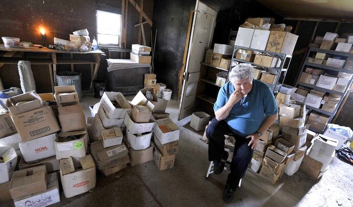 In this Aug. 6, 2019, photo, Robert Wolf, of Fort Dodge, Iowa, sits among the boxes of rock specimens he's donating to the University of Iowa. Wolf has spent a lifetime collecting the specimens in Iowa and he's carefully cataloged each piece. He also donated part of the rock collection to the University of Pittsburgh and his book collection to the University of Northern Iowa. Wolf is moving into an apartment and no longer has room for the collection which he's taken a lifetime to build. (Hans Madsen /The Messenger via AP)