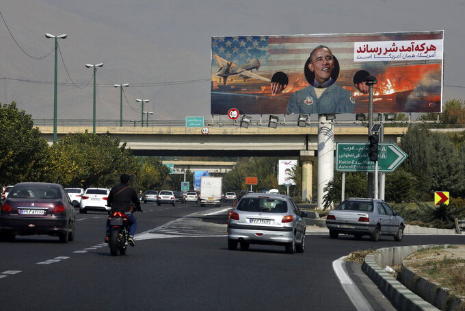 """Vehicles drive on a highway under an anti-U.S. billboard with a portrait of former President Barack Obama, in Tehran, Iran, Tuesday, Nov. 3, 2020. The coronavirus pandemic forced authorities to cancel a planned commemoration of the Nov. 4, 1979 takeover of the U.S. Embassy in Tehran. The Persian writings on the billboard reads: """"Whoever came inflicted evil. America remains the same."""" (AP Photo/Vahid Salemi)"""