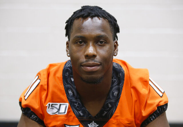 FILE - In this Aug. 3, 2019, file photo, Oklahoma State linebacker Amen Ogbongbemiga poses during an NCAA college football media day in Stillwater Okla. Oklahoma State University officials said Wednesday, June 3, 2020, that  three returning student-athletes have tested positive for COVID-19 although they were not showing symptoms. Among them is OSU linebacker Amen Ogbongbemiga, who said on Twitter he tested positive for the virus after he attended a protest in Tulsa. The 21-year-old Ogbongbemiga says he protected himself during the protest. (AP Photo/Sue Ogrocki, File)
