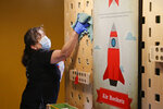 Corina Guerra cleans an interactive display at Science Museum Oklahoma, Monday, June 1, 2020, in Oklahoma City as the museum reopens with limited capacity and social distancing requirements. Employees are required to wear masks and guests are encouraged to wear masks. (AP Photo/Sue Ogrocki)