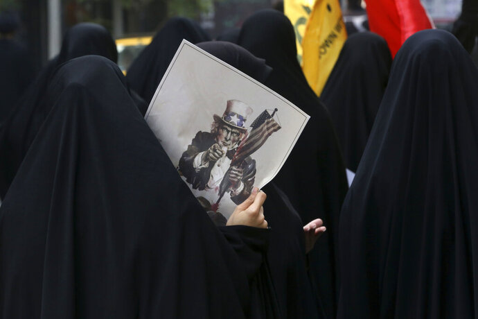 FILE - In this Oct. 4, 2015 file photo, a female Iranian demonstrator holds a poster showing a caricature of Uncle Sam during an annual anti-U.S. rally in front of the former U.S. Embassy in Tehran, Iran. (AP Photo/Vahid Salemi, File)