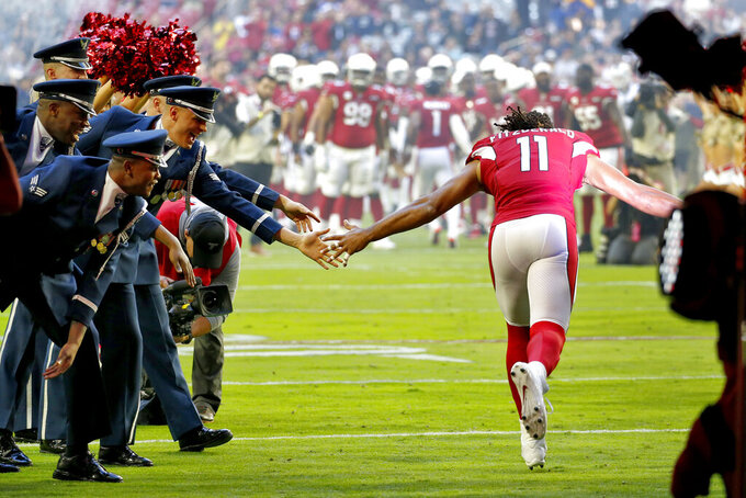 Arizona Cardinals wide receiver Larry Fitzgerald (11) greets Military personnel as he takes the field prior to an NFL football game against the Los Angeles Rams, Sunday, Dec. 1, 2019, in Glendale, Ariz. (AP Photo/Ross D. Franklin)