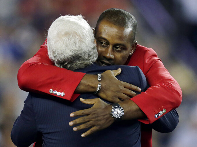 FILE - In this Oct. 16, 2014, file photo, former New England Patriots cornerback Ty Law, rear, hugs New England Patriots owner Robert Kraft during a ceremony honoring him as the newest member of the Patriots Hall of Fame, during halftime of an NFL football game between the Patriots and the New York Jets, in Foxborough, Mass. Law will be inducted into the Pro Football Hall of Fame in Canton, Ohio on Aug. 3, 2019. (AP Photo/Charles Krupa, File)