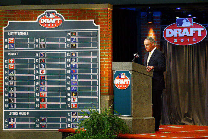 FILE - In this June 9, 2016, file photo, Major League BaseballCommissioner Rob Manfred speaks during the MLB draft, in Secaucus, N.J. Major League Baseball will cuts its amateur draft from 40 rounds to five this year, a move that figures to save teams about $30 million. Clubs gained the ability to reduce the draft as part of their March 26 agreement with the players' association and MLB plans to finalize a decision next week to go with the minimum, a person familiar with the decision told The Associated Press. The person spoke Friday, May 8, 2020, on condition of anonymity because no decision was announced. (AP Photo/Julio Cortez, File)