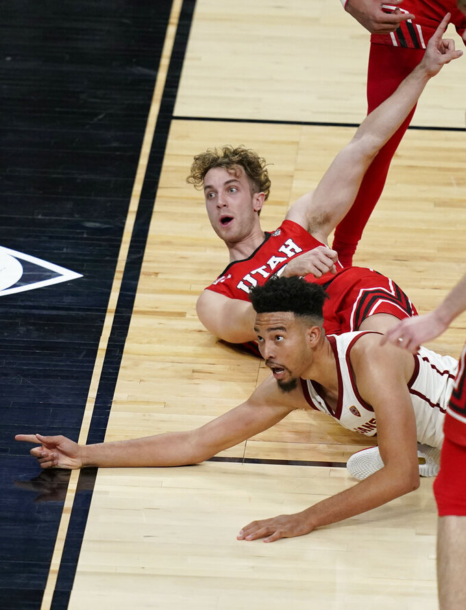 Southern California's Isaiah Mobley, bottom, and Utah's Jaxon Brenchley (5) react after a play during the second overtime of an NCAA college basketball game in the quarterfinal round of the Pac-12 men's tournament Thursday, March 11, 2021, in Las Vegas. (AP Photo/John Locher)